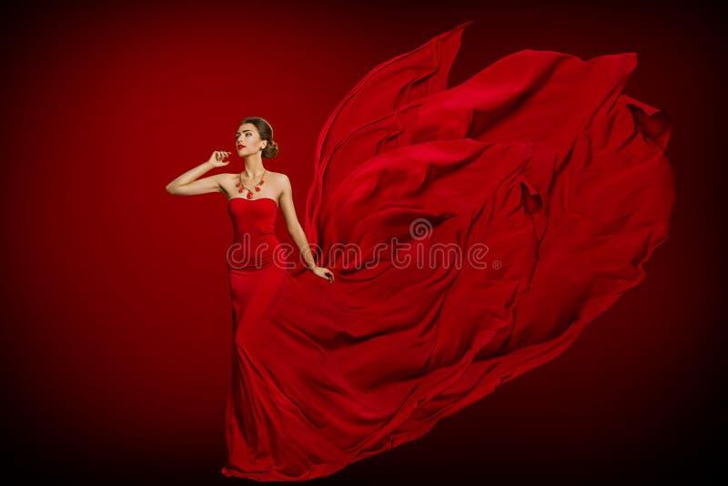 Modemodell Red Flaming Dress, kvinna i långt den vinkande kappasvansen för fladdra, ung flickaskönhetstående royaltyfri foto