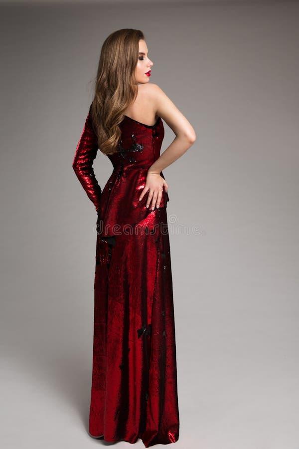 Modemodell Red Sparkling Dress, elegant kvinna i den långa aftonkappan, bakre sikt royaltyfri bild