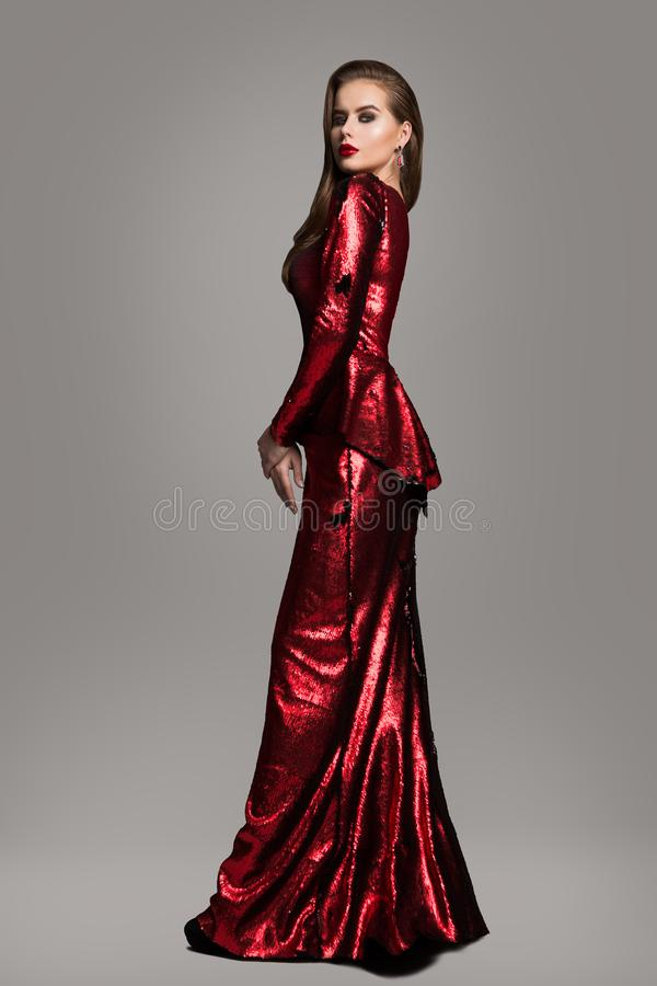 Modemodell Red Sparkling Dress, elegant kvinna i den långa aftonkappan, härlig flickaskönhetstående royaltyfri foto