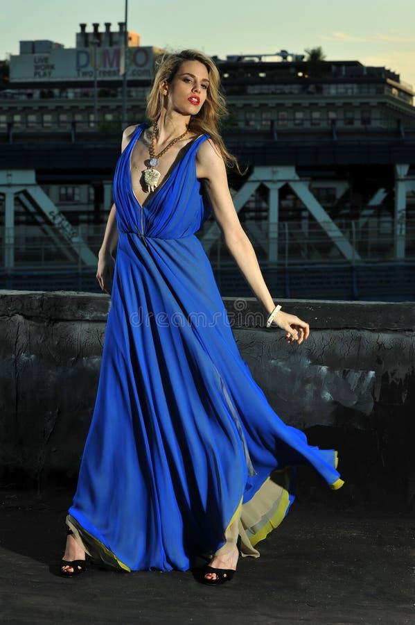 Modemodell som poserar den sexiga bärande långa blåa aftonklänningen på takläge arkivbild
