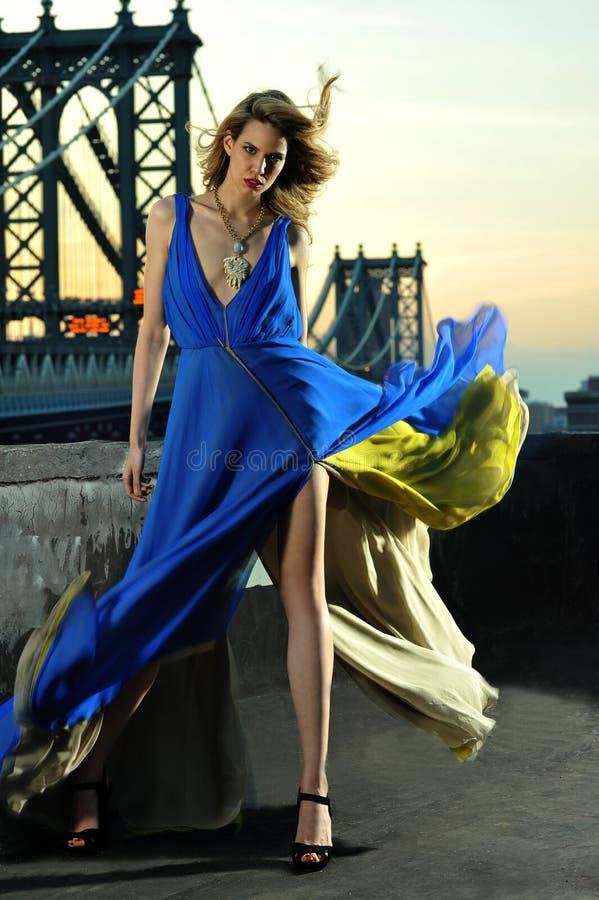 Modemodell som poserar den sexiga bärande långa blåa aftonklänningen på takläge royaltyfria bilder