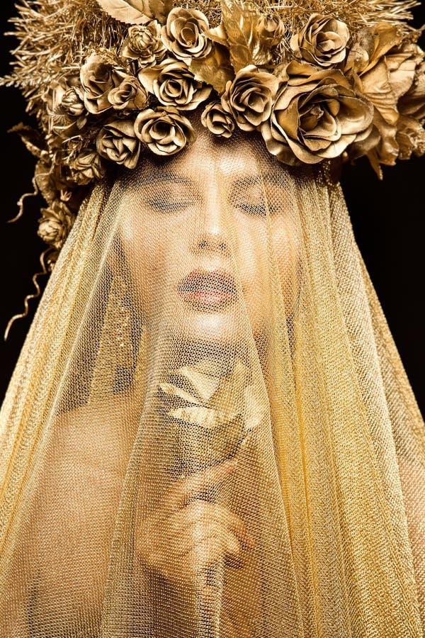 Modemodellen i guld- blommahatt skyler, den härliga kvinnan Art Portrait med guld- Rose Flower fotografering för bildbyråer