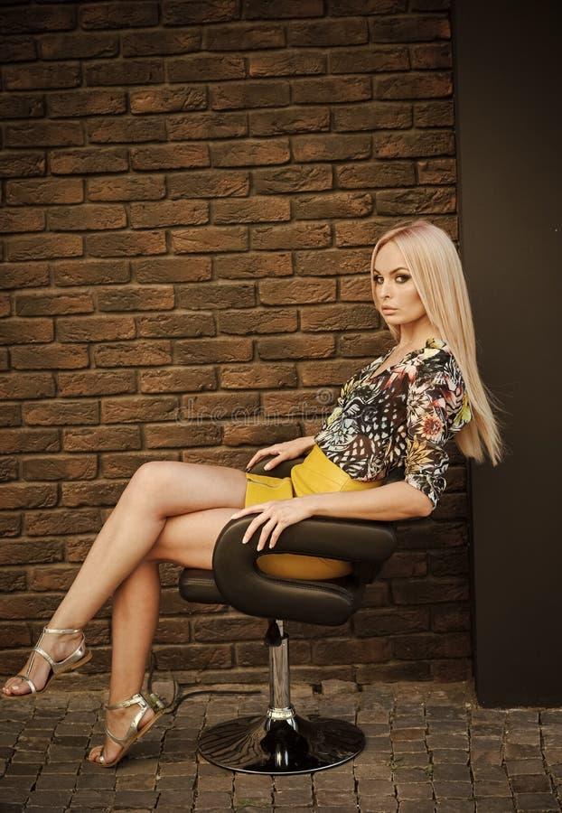Modemodellen i trendig kläder sitter i fåtölj Den sexiga kvinnan har hennes stil, mode Kvinna med långt blont hår och royaltyfria bilder