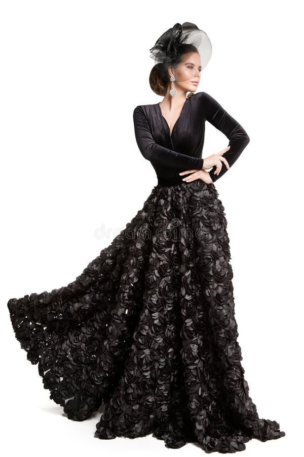 Modemodellen Long Black Dress, den eleganta kvinnan i hatt skyler, skönhetståenden på vit royaltyfria bilder