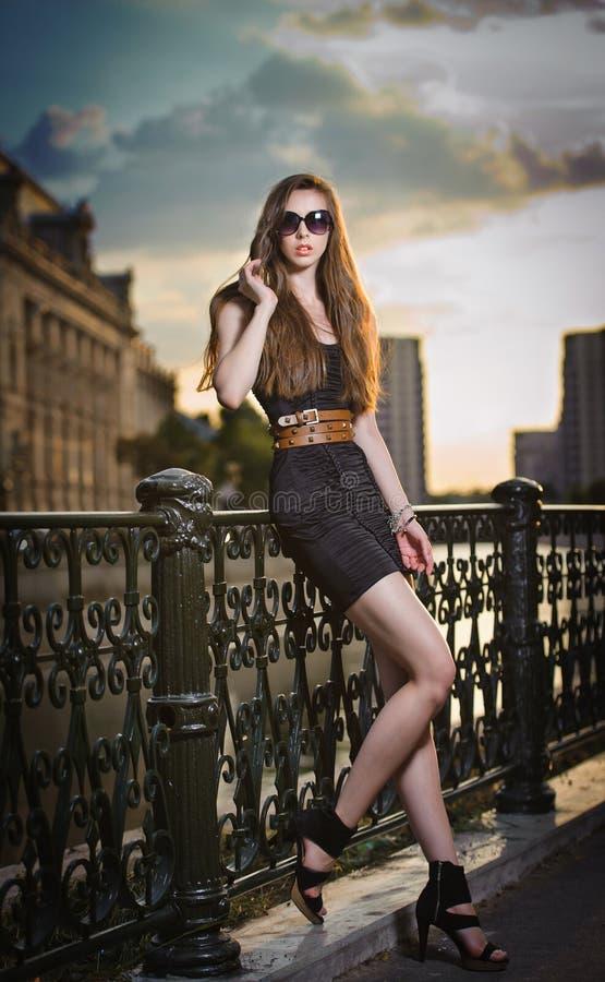 Modemodellen på gatan med solglasögon och kortslutningssvart klär royaltyfri foto
