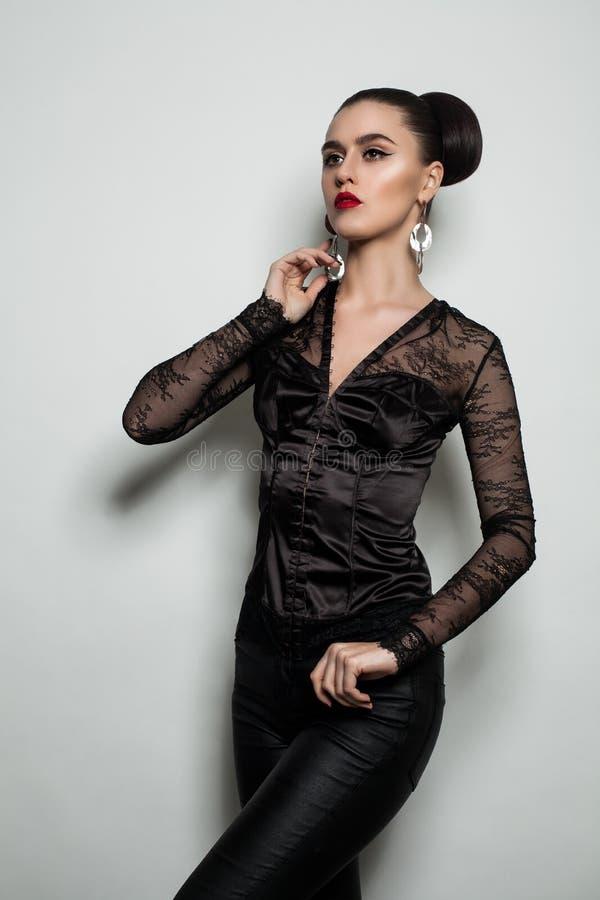 Modemodellen Woman i svart beklär anseende mot Gray Wall fotografering för bildbyråer