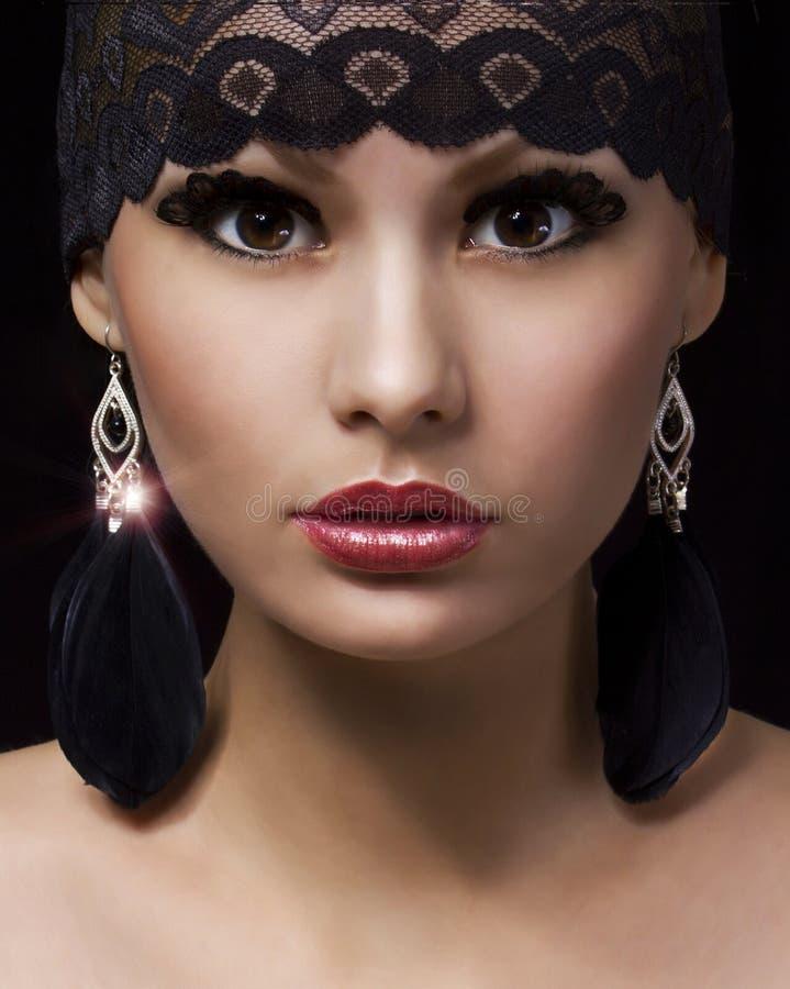 Modemuslimstående. Den härliga zigenska unga kvinnan med yrkesmässig makeup och snör åt tillbehör över svart royaltyfria bilder