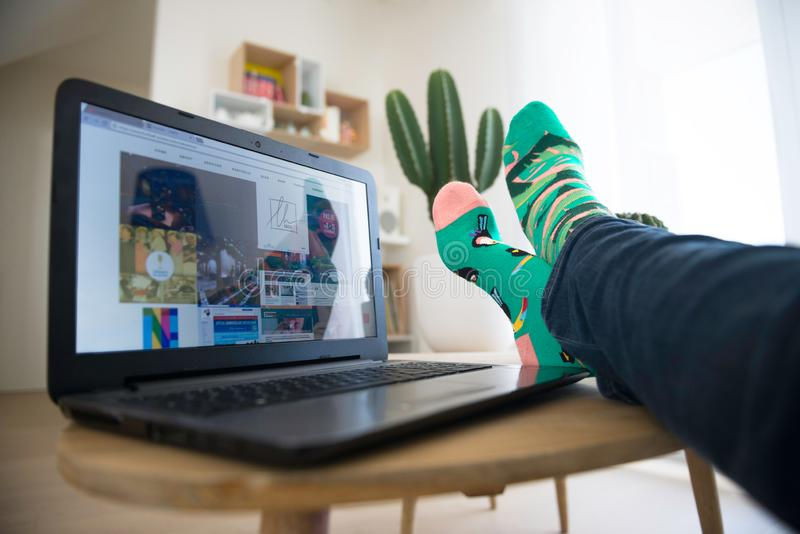 Modena, Italy, 04/07/2018 : A man in crazy multi-coloured socks with feet on table with a laptop computer at home stock photo