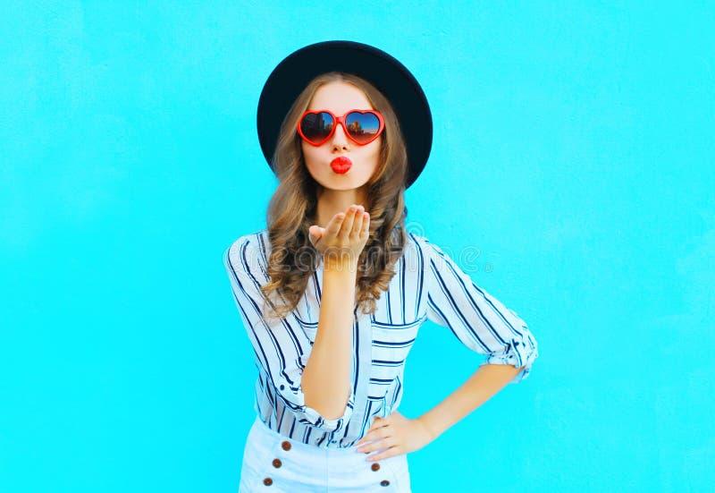 Modeporträt, das hübsche Frau mit den roten Lippen ist, sendet einen Luftkuß in einer Sonnenbrilleform des Herzens über Blau stockfoto