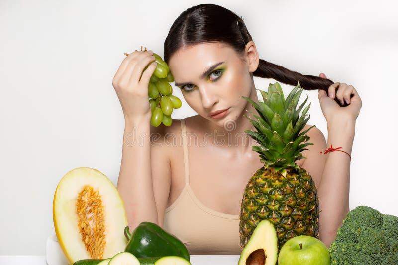 Modeportr?t der jungen attraktiven brunette Frau, die durch die Tabelle mit Obst und Gem?se sitzt, Trauben herein halten stockfotos