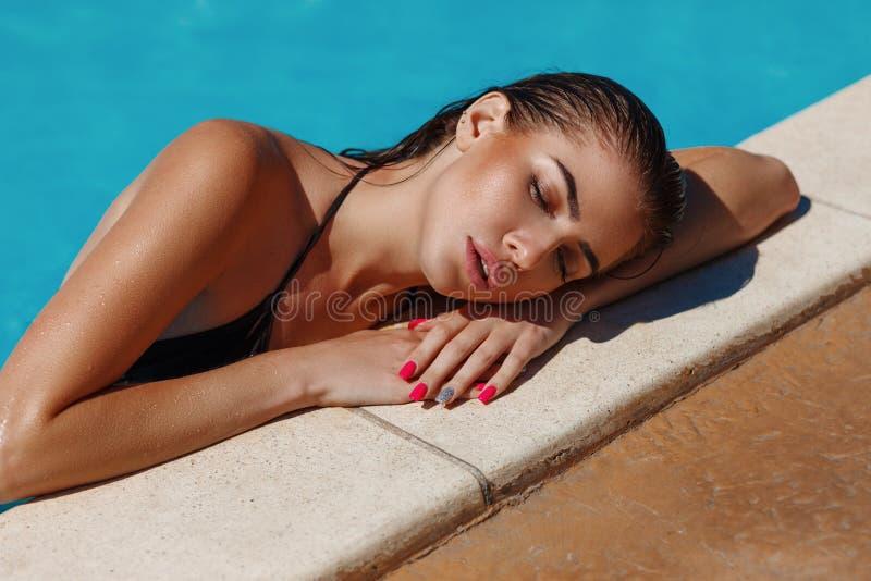 Modeporträt der schönen sexy gebräunten sportlichen dünnen Frau, die im Swimmingpoolbadekurort sich entspannt Sitzzahl mit netten stockfoto