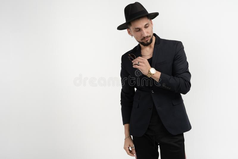 Modeportr?t des h?bschen eleganten Mannes im schwarzen Anzug und im Hut mit Sonnenbrille in der Hand, unten schauend und werfen i lizenzfreies stockfoto