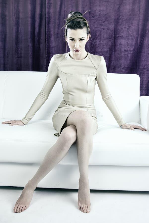 Modeporträt des Modells mit erstaunlichem verrücktem Make-up und Haar tun die Zukunftsromane, die auf Couch sitzen stockbild