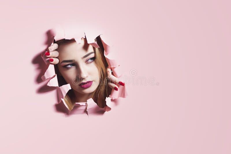 Modeporträt einer jungen Frau, die ein Loch im rosa Papppapier, Gesicht eines Mädchens mit Make-up, kreatives Konzept zerreißt lizenzfreies stockfoto