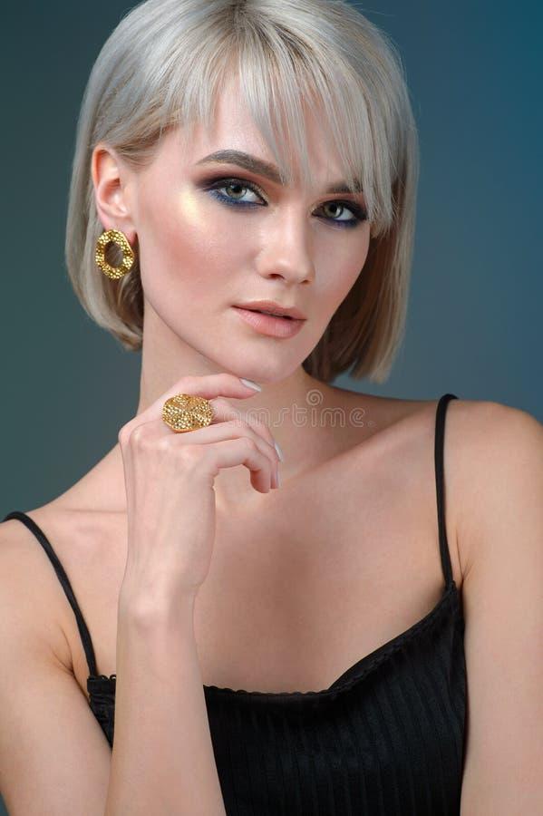 Modeporträt einer schönen jungen Frau in stilvollem Stilvolles Frisur- und Lichtmake-up Tragender Ohrring- und Fingerring lizenzfreie stockfotos