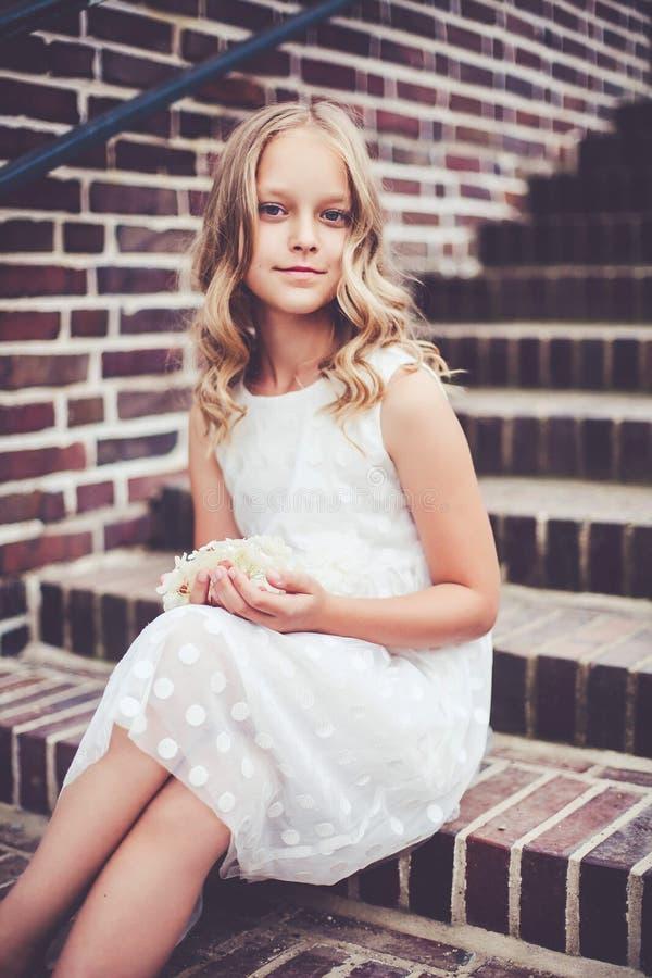 Modeporträt eines schönen 9-10-jährigen lächelnden Mädchens, das auf der Treppe sitzt stockfotos