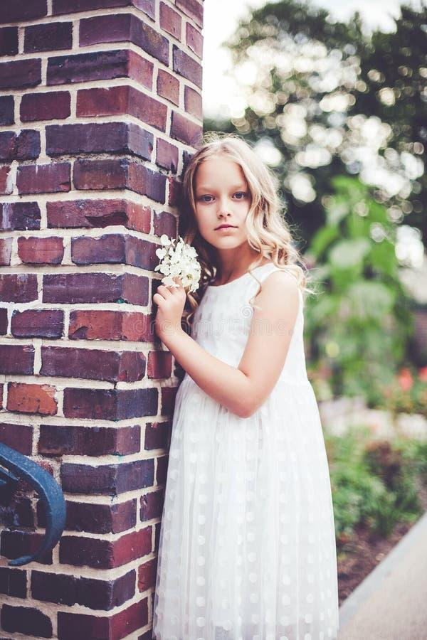 Modeporträt eines schönen 9-10-jährigen Mädchens, das weißes Kleid trägt und im Park posiert lizenzfreie stockfotografie