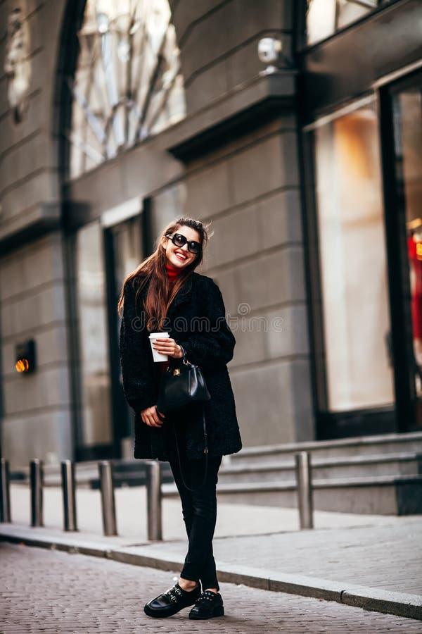 Modeporträt im Freien der stilvollen jungen Frau, die Spaß, emotionales Gesicht, Lachen, Kamera betrachtend hat Hält Kaffee lizenzfreie stockfotografie