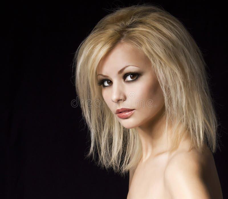 Modeporträt. Schöne Blondine mit Berufsmake-up und Frisur, über Schwarzem. Vogue-Artmodell lizenzfreies stockbild