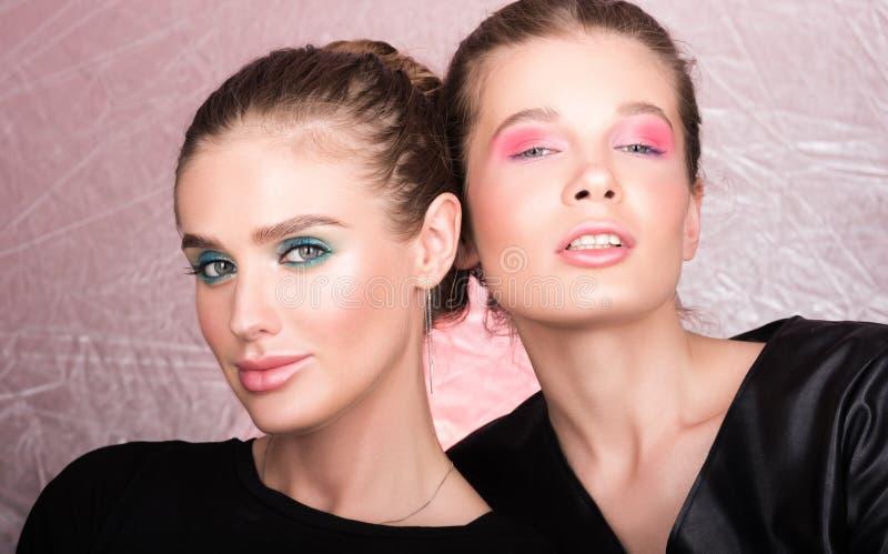 Modeporträt von zwei schönen jungen Frauen Helles Berufsmake-up stockbilder