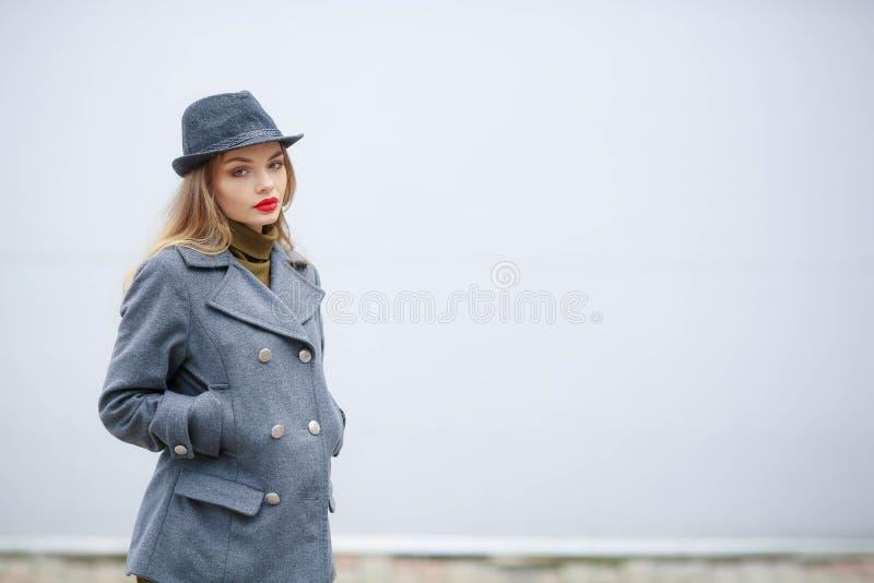 Modeportr?t im Freien der jungen sch?nen modernen Frau, die stilvolle Zus?tze tr?gt Weinlesehut, Kamera betrachtend lizenzfreie stockfotos