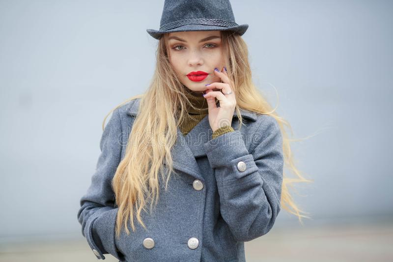 Modeportr?t im Freien der jungen sch?nen modernen Frau, die stilvolle Zus?tze tr?gt Weinlesehut, Kamera betrachtend lizenzfreie stockfotografie