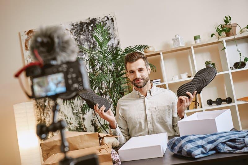 Moderådgivning Le manliga skor för sport för modebloggervisning på kamera, medan anteckna den nya videoen för hans mode royaltyfria foton