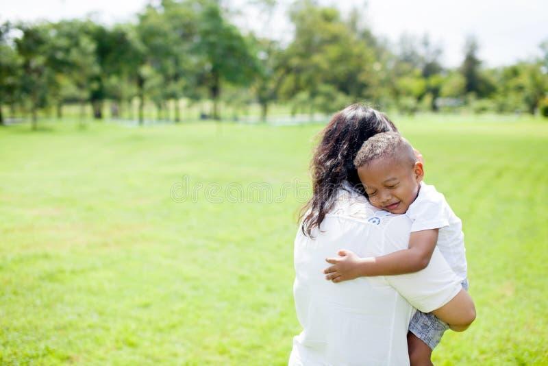 Moder av den blandade afrikansk amerikanpojken som bär hennes unge i parkera royaltyfri fotografi