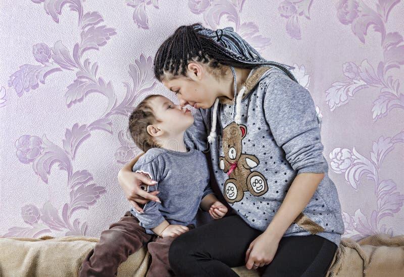 Moder barn, pojke som är lycklig, familj, hem som ler, barndom som är gullig, arkivfoto
