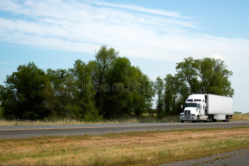 Moder bonnet white big rig semi truck with reefer trailer delivering commercial cargo by flat road in California. Big classic American binnet brilliant white stock photography