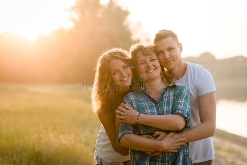Moder, dotter och son som tillsammans poserar Familjbindning royaltyfri fotografi