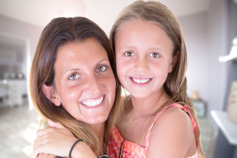 Moder för husfamiljskönhet och barndotter som hemma huging arkivfoton