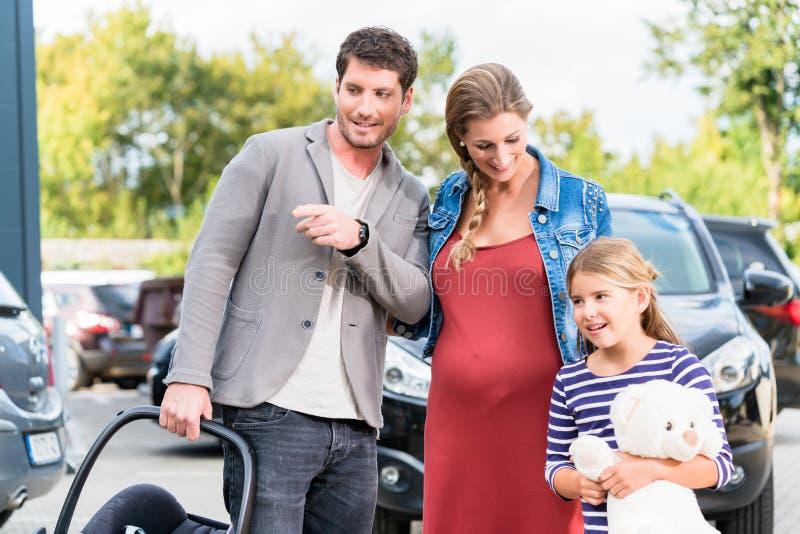 Moder, fader och barnköpandebil på återförsäljaren royaltyfri bild
