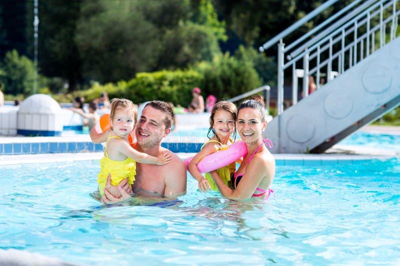 Moder, fader och döttrar i simbassäng solig sommar royaltyfri bild