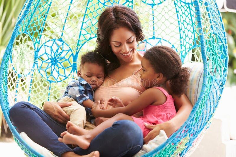Moder med barn som kopplar av på utomhus- trädgårds- gunga Seat royaltyfri foto