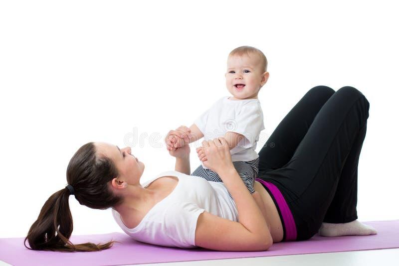 Moder med barnpojken som gör konditionövningar arkivfoto