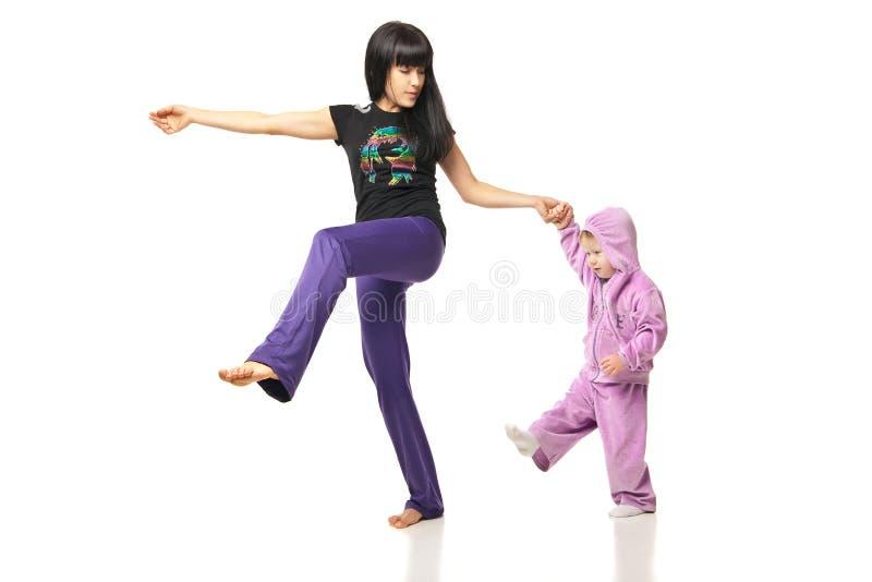 Moder med behandla som ett barn som gör övningar över vit royaltyfria foton