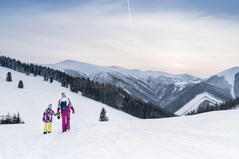 Moder med daugher som går handen - i - hand vid snömoontainslingan Aktiv utomhus- bild för tidutgifterbegrepp royaltyfria bilder