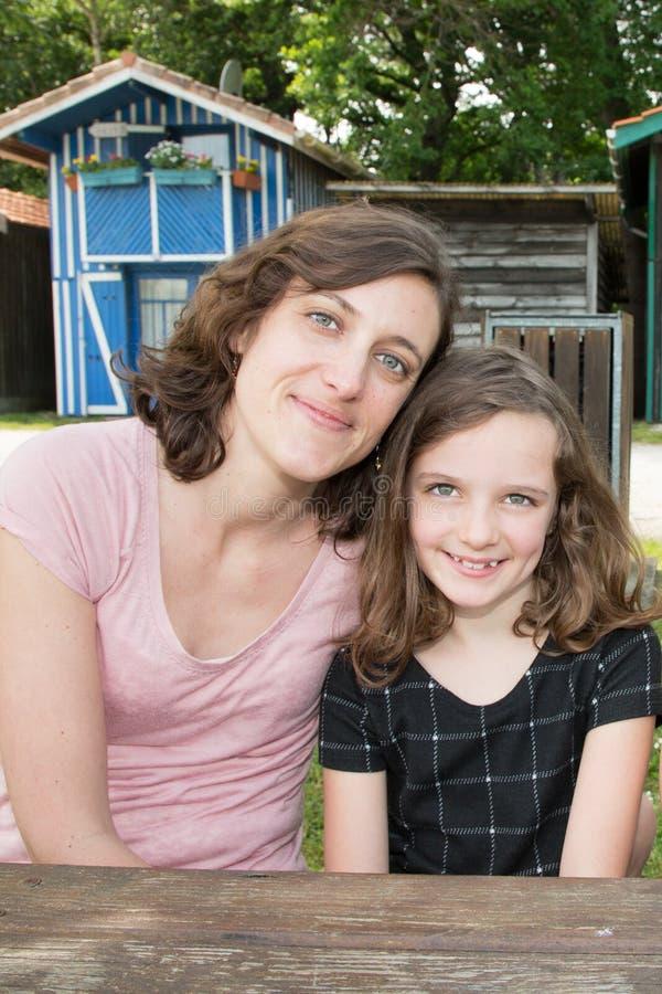 Moder med den gladlynta dotterbarnflickan som är utomhus- i semester arkivbild