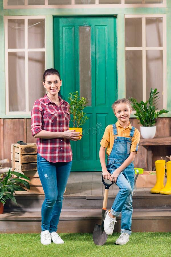 Moder med den inlagda växten och dottern med den trädgårds- skyffeln som ser kameran royaltyfria foton