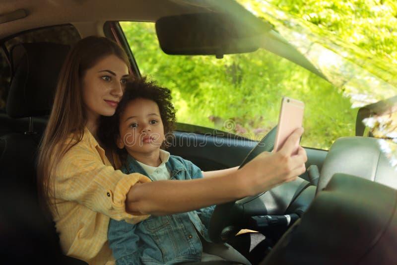Moder med den lilla dottern som kör bilen och tar selfie arkivfoton