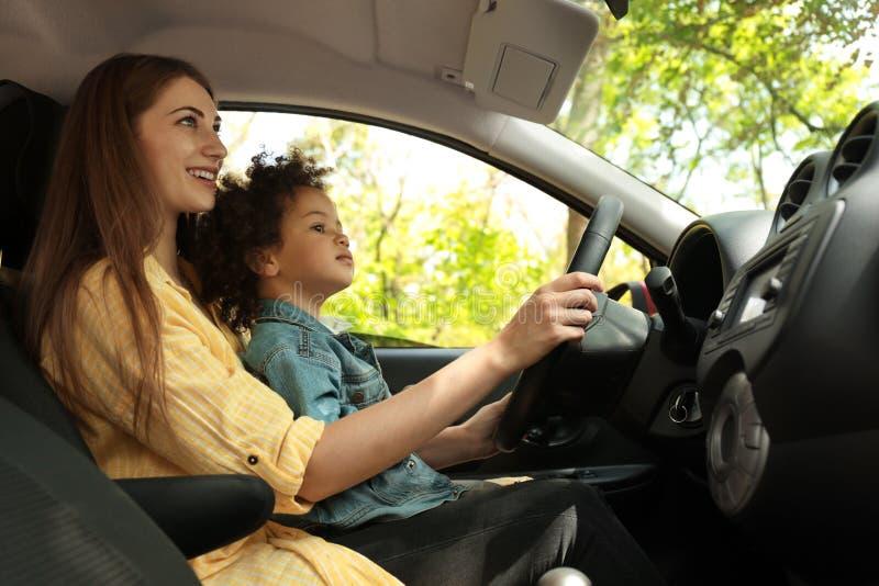 Moder med den lilla dottern som tillsammans kör bilen BARN I FARA arkivbild