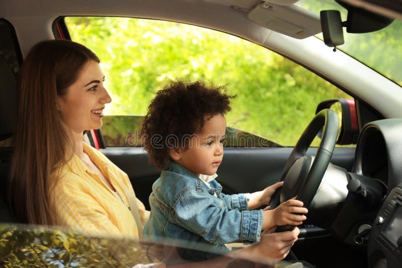 Moder med den lilla dottern som tillsammans kör bilen BARN I FARA arkivfoto