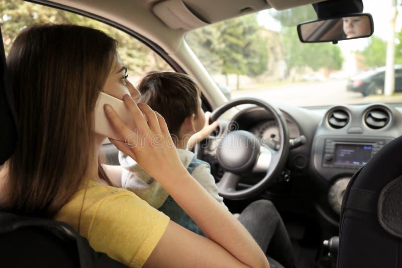 Moder med den lilla sonen på knä som kör bilen och talar vid telefonen arkivfoton