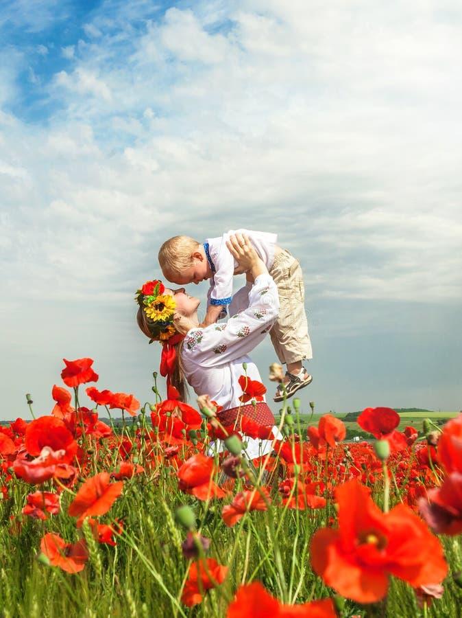 Moder med den lilla sonen på vallmofältet fotografering för bildbyråer