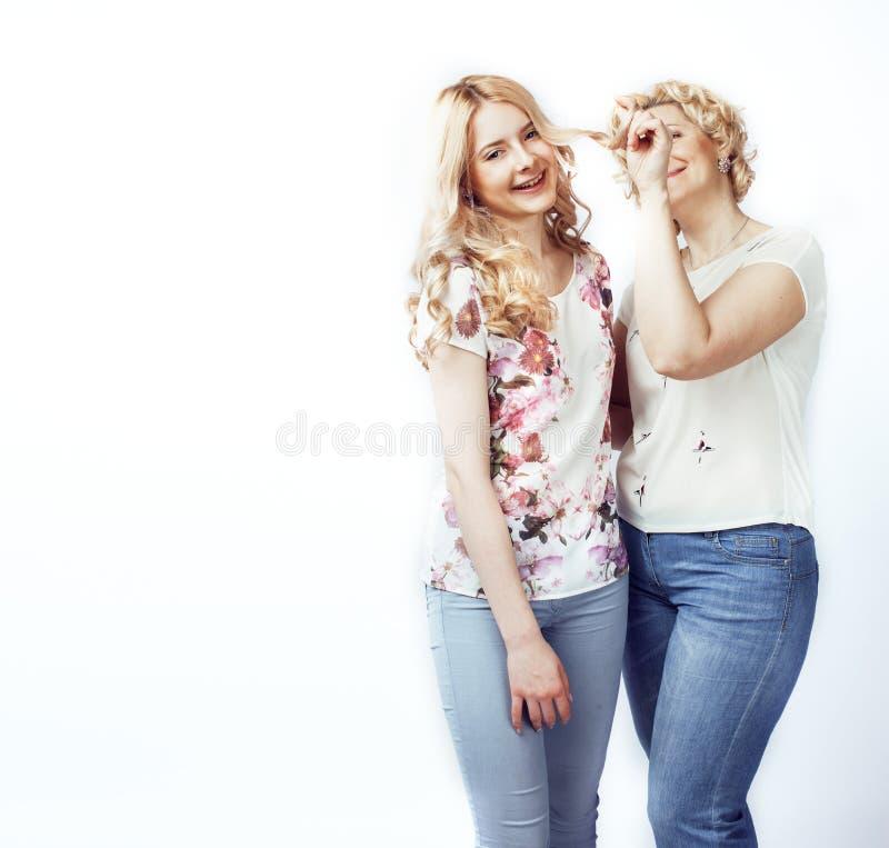 Moder med den tonåriga dottern som poserar tillsammans lyckligt isolerat le arkivbild