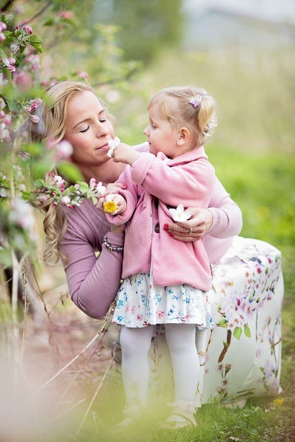 Moder med det lilla litet barndotterinnehavet och luktaäpplet tr royaltyfria foton