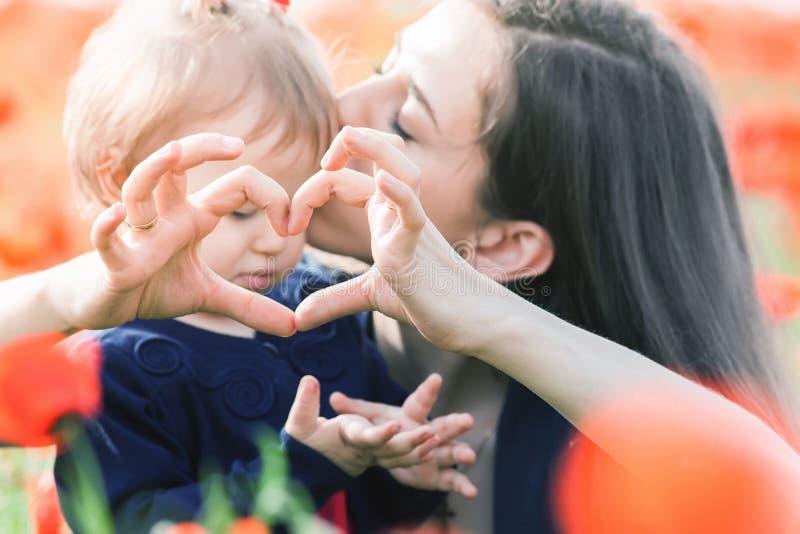 Moder med det roliga barnet som är utomhus- på vallmoblommafältet royaltyfri fotografi