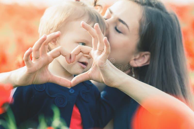 Moder med det roliga barnet som är utomhus- på vallmoblommafältet fotografering för bildbyråer