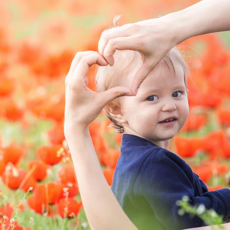 Moder med det roliga barnet som är utomhus- på vallmoblommafältet royaltyfri foto